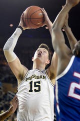 Michigan center Jon Teske shoots past UMass Lowell guard Christian Lutete during the second half.