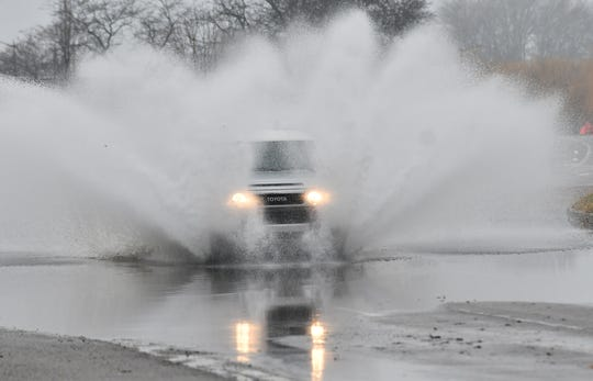 A vehicle drives through a large puddle on The Strand on Belle Isle in Detroit on Dec. 29, 2019.