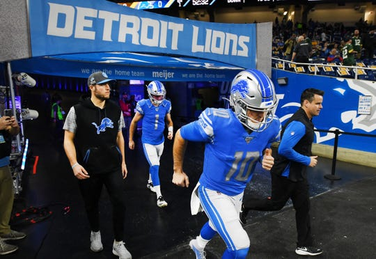 Lions quarterback David Blough leads injured Matthew Stafford and backup quarterback Kyle Slater onto the field for warmups.