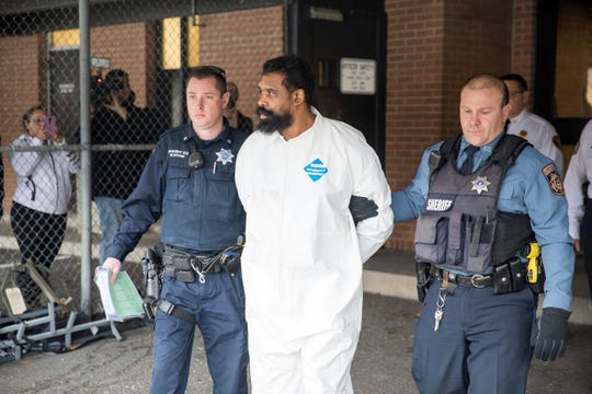 Ramapo police officers escort Grafton Thomas from Ramapo Town Hall to a police vehicle, Sunday, Dec. 29, 2019, in Ramapo, N.Y. Thomas is accused of stabbing multiple people as they gathered to celebrate Hanukkah at a rabbi's home in the Orthodox Jewish community north of New York City. (AP Photo/Julius Constantine Motal)