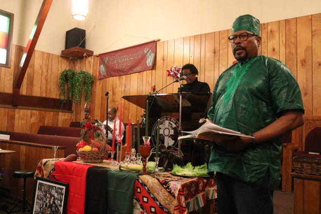 Dr. James Williams describes each of the seven principles of Kwanzaa during a service at the Ebenezer Church of God in Christ on Saturday.