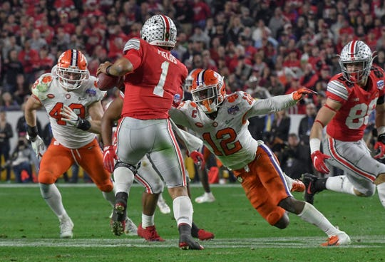 Clemson defensive back K'Von Wallace (12) sacks Ohio State quarterback Justin Fields(1) near linebacker Chad Smith (43) during the third quarter of the PlayStation Fiesta Bowl of the College Football Playoffs semi-final game, at State Farm Stadium in Glendale, Arizona Saturday, December 28, 2019.
