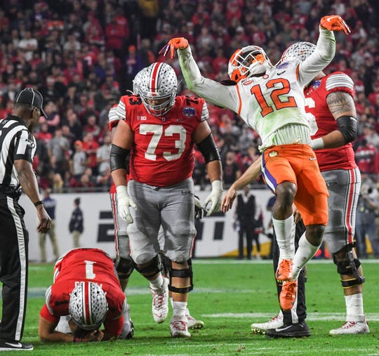 Clemson defensive back K'Von Wallace (12) jumps up for a kick dance like a scene from the Karate Kid movie after sacking Ohio State quarterback Justin Fields(1) during the fourth quarter of the PlayStation Fiesta Bowl of the College Football Playoffs semi-final game, at State Farm Stadium in Glendale, Arizona Saturday, December 28, 2019.