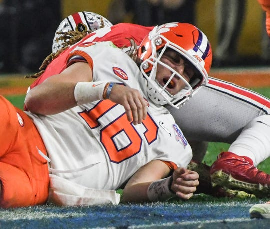 Clemson quarterback Trevor Lawrence (16) rolls around after being sacked by Ohio State corner back Shaun Wade(24) during the second quarter of the PlayStation Fiesta Bowl of the College Football Playoffs semi-final game, at State Farm Stadium in Glendale, Arizona Saturday, December 28, 2019. Wade was ejected for targeting.