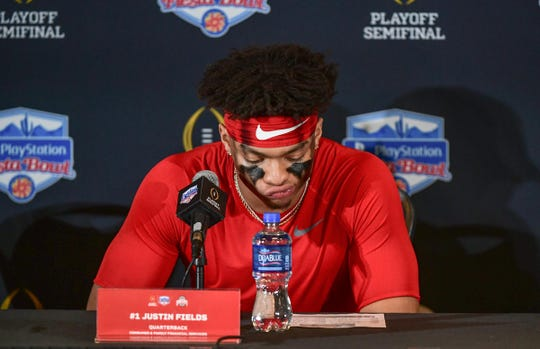 Ohio State quarterback Justin Fields(1) waits for the post game press conference to begin following a 29-23 loss to Clemson in the PlayStation Fiesta Bowl of the College Football Playoffs semi-final game, at State Farm Stadium in Glendale, Arizona Saturday, December 28, 2019.