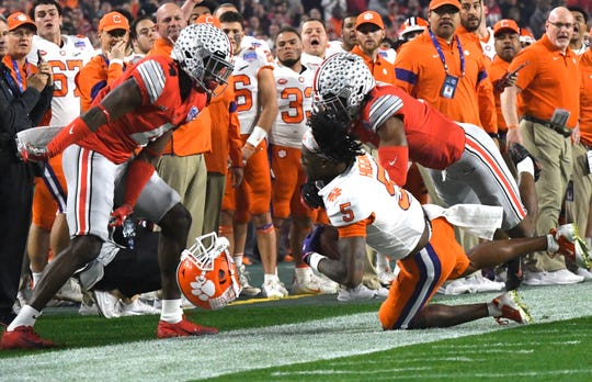 Clemson wide receiver Tee Higgins (5) is hit by an Ohio State defender during the Fiesta Bowl on Saturday, Dec. 28, 2019.