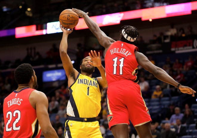 Indiana Pacers forward T.J. Warren (1) shoots over New Orleans Pelicans guard Jrue Holiday (11) during the first quarter at the Smoothie King Center.
