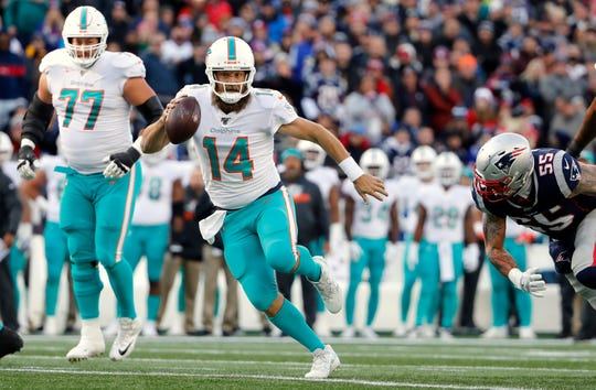 Dec 29, 2019; Foxborough, Massachusetts, USA; Miami Dolphins quarterback Ryan Fitzpatrick (14) scrambles past New England Patriots defensive end John Simon (55) during the first half at Gillette Stadium.