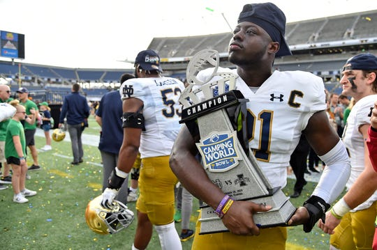 Notre Dame Fighting Irish safety Jalen Elliott (21) poses with the winners trophy after defeating the Iowa State Cyclones at Camping World Stadium.