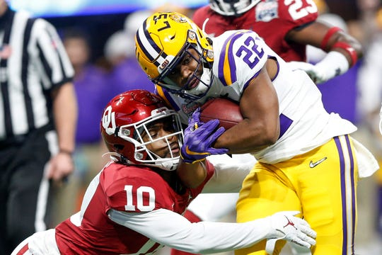 Oklahoma safety Pat Fields (10) hits LSU running back Clyde Edwards-Helaire (22) during the first half of the Peach Bowl NCAA college football playoff semifinal in Atlanta on Saturday, Dec. 28, 2019. (Ian Maule/Tulsa World via AP)