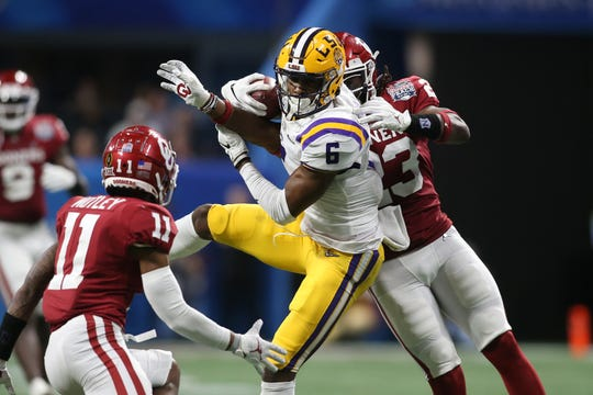 Dec 28, 2019; Atlanta, Georgia, USA; LSU Tigers wide receiver Terrace Marshall Jr. (6) catches a pass against Oklahoma Sooners cornerback Parnell Motley (11) and linebacker DaShaun White (23) during the third quarter of the 2019 Peach Bowl college football playoff semifinal game. Mandatory Credit: Brett Davis-USA TODAY Sports