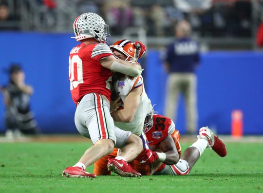 Clemson quarterback Trevor Lawrence gets sandwiched between Ohio State linebacker Pete Werner and defensive end Zach Harrison during Saturday's College Football Playoff semifinal at the Fiesta Bowl.