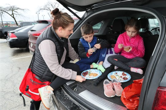 People took advantage of the warm weather Sunday to visit the Milwaukee County Zoo during its Frosty Free Week. The zoo is free through New Year's Day. Here, Lindsay Heus of Richfield and her children, William, 6, center, and Gracyn, 8, enjoy a picnic lunch in the zoo's parking lot.