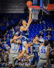 Rhode Island's Jeff Dowtin (11) slices his way through multiple MTSU defenders for the basket on Sunday.