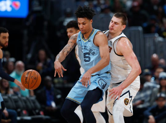 Memphis Grizzlies forward Brandon Clarke, left, has the ball knocked out of his control by Denver Nuggets center Nikola Jokic in the first half on Saturday, Dec. 28, 2019, in Denver.