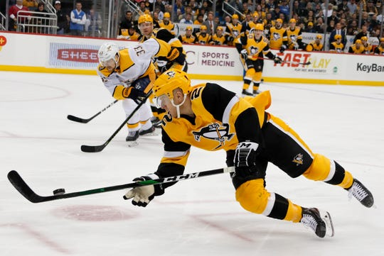 Pittsburgh Penguins' Chad Ruhwedel (2) dives to control the puck in front of Nashville Predators' Viktor Arvidsson (33) during the second period Saturday in Pittsburgh.