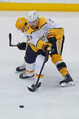 Nashville Predators' Viktor Arvidsson (33) brings the puck up ice as Pittsburgh Penguins' Jake Guentzel defends during the first period Saturday, Dec. 28, 2019, in Pittsburgh.