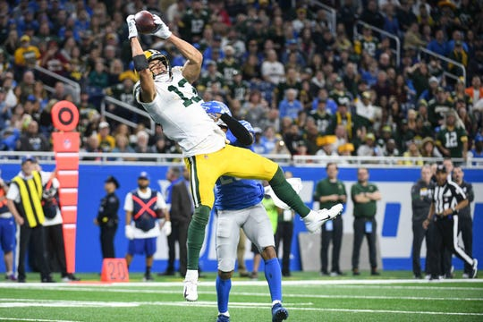 Green Bay Packers wide receiver Allen Lazard (13) completes a touchdown as Detroit Lions cornerback Darius Slay (23) defends during the fourth quarter at Ford Field.