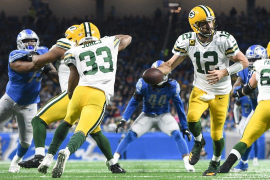 Green Bay Packers quarterback Aaron Rodgers (12) looks to hand off to running back Aaron Jones (33) during the second quarter against the Detroit Lions at Ford Field.
