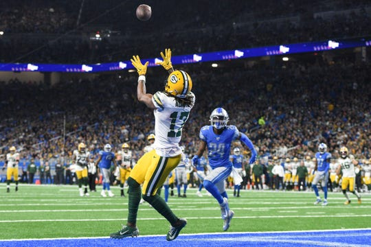 Green Bay Packers wide receiver Davante Adams (17) completes a touchdown pass during the third quarter against the Detroit Lions at Ford Field.