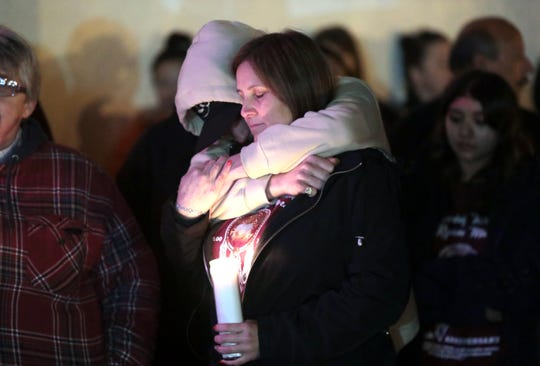 Alex Ryan Marcotte's mother, Jeanette Burns, is hugged by Alex's friend Blake Sumner, 19, during a candlelight vigil for  Marcotte on the one-year anniversary of his death in Banning, Calif., on Saturday, December 28, 2019.
