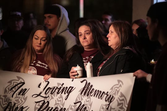 Dylan Artea's aunt, Jennifer Blistan, left, and mother, Kelly Blistan, stand next to Alex Ryan Marcotte's mother, Jeanette Burns, during a candlelight vigil for Alex Ryan Marcotte on the one-year anniversary of his death in Banning, Calif., on Saturday, December 28, 2019. Dylan Artea was also shot and survived but became paralyzed. Police are still looking for the suspect.