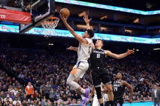 Phoenix Suns guard Devin Booker, left, goes to the basket against Sacramento Kings guard Bogdan Bogdanovic, right, during the second half of an NBA basketball game in Sacramento, Calif., Saturday, Dec. 28, 2019. (AP Photo/Hector Amezcua)