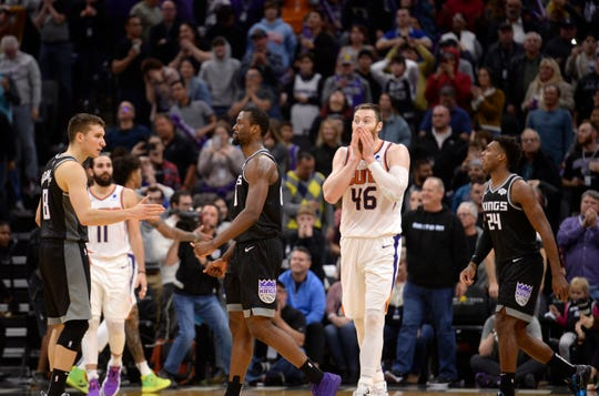 Phoenix Suns center Aron Baynes, second from right, reacts to his team's 112-110 victory over the Sacramento Kings in an NBA basketball game in Sacramento, Calif., Saturday, Dec. 28, 2019. Kings forward Harrison Barnes, center, who missed a 3-point attempt, is greeted by guard Bogdan Bogdanovic, left, (AP Photo/Hector Amezcua)