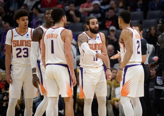 Phoenix Suns guard Ricky Rubio, second from right, talks with teammate Elie Okobo, right, during the first quarter of an NBA basketball game against the Sacramento Kings in Sacramento, Calif., Saturday, Dec. 28, 2019. (AP Photo/Hector Amezcua)