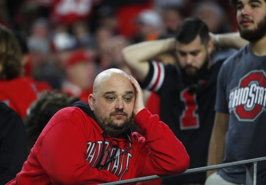 Dec 28, 2019; Glendale, AZ, USA;  Ohio State fans react after Clemson's victory in the 2019 Fiesta Bowl college football playoff semifinal game at State Farm Stadium. Mandatory Credit: Patrick Breen/Arizona Republic via USA TODAY NETWORK