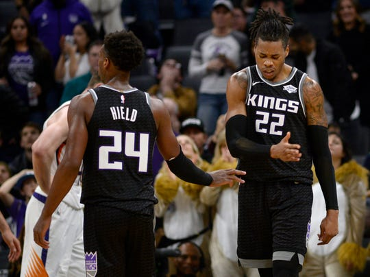 Sacramento Kings forward Richaun Holmes, right, reacts to a missed free throw as he slaps hands with guard Buddy Hield (24) during the fourth quarter of the team's NBA basketball game against the Phoenix Suns in Sacramento, Calif., Saturday, Dec. 28, 2019. (AP Photo/Hector Amezcua)