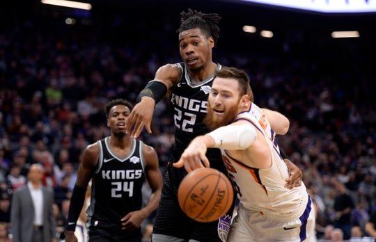 Phoenix Suns center Aron Baynes, right, and Sacramento Kings forward Richaun Holmes, center, reach for the ball during the second half of an NBA basketball game in Sacramento, Calif., Saturday, Dec. 28, 2019. (AP Photo/Hector Amezcua)