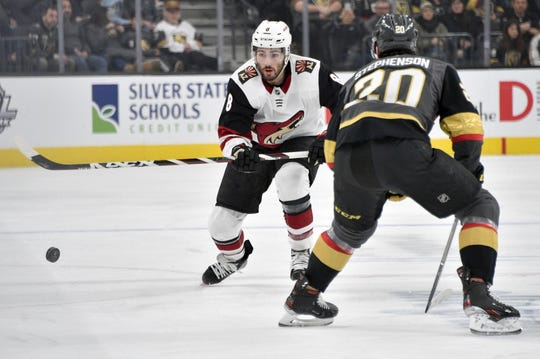 Arizona Coyotes center Nick Schmaltz (8) skates with the puck against Vegas Golden Knights center Chandler Stephenson during the first period of an NHL hockey game Saturday, Dec. 28, 2019, in Las Vegas. (AP Photo/David Becker)