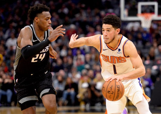 Sacramento Kings guard Buddy Hield, left, defends Phoenix Suns guard Devin Booker (1) as he drives to the basket during the second half of an NBA basketball game in Sacramento, Calif., Saturday, Dec. 28, 2019. (AP Photo/Hector Amezcua)