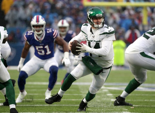 Jets quarterback Sam Darnold has to roll away from pressure by Bills Julian Stanford.