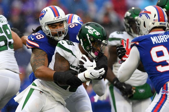 Dec 29, 2019; Orchard Park, New York, USA; New York Jets running back Le'Veon Bell (26) runs with the ball while being tackled by Buffalo Bills defensive tackle Star Lotulelei (98) during the first quarter at New Era Field.