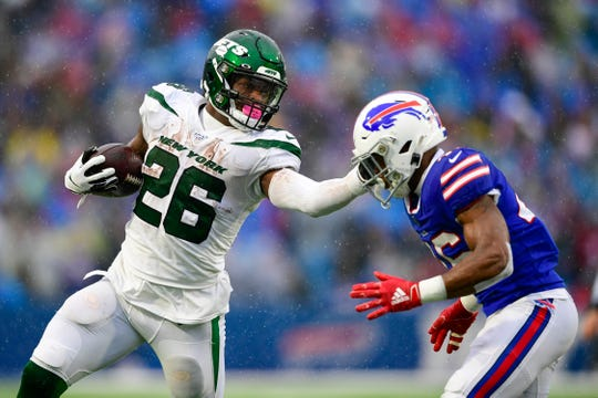 New York Jets running back Le'Veon Bell (26) stiff-arms Buffalo Bills' Jaquan Johnson (46) during the first half of an NFL football game Sunday, Dec. 29, 2019 in Orchard Park.