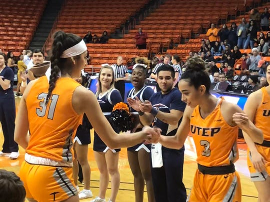 Katia Gallegos (3) bumps fists with Tatania Modawar before Sunday's game against Tulsa at the Don Haskins Center