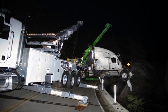 A tractor-trailer is hauled out of Matilija Creek onto Highway 33 above Ojai on Dec. 26, 2019. No serious injuries were reported.