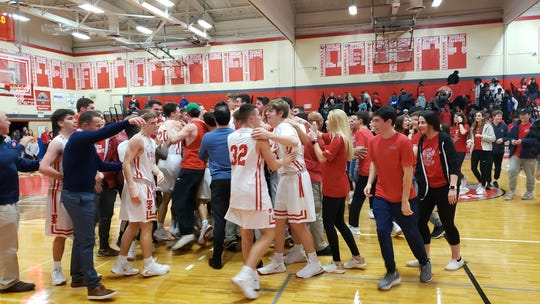 Tappan Zee students storm the court to celebrate with the players, after beating Poughkeepsie, 69-60 on Saturday night.