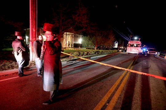 Hasidic Jewish men stand outside the home of a rabbi on Forshay Rd. in Monsey, N.Y. Sunday night after a man entered the house and stabbed multiple people who were there for a Hanukkah gathering.