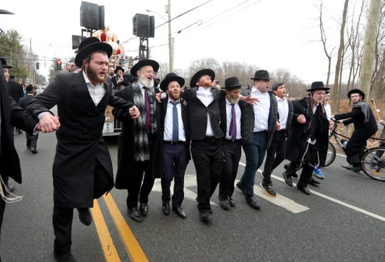 Hasidic Jews take part in a procession celebrating the completion of the writing of a new Torah Scroll in Monsey Dec. 28, 2019. The procession took place less than 24 hours after a man entered the home of a rabbi in Monsey and stabbed five people during a Hanukkah celebration. The Torah procession made a stop in front of the rabbi's house as a show of solidarity in the community.