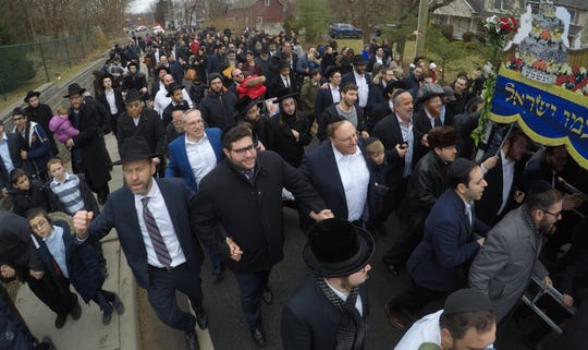 A procession for a new Torah near a rabbi's home where a stabbing occurred the night before Dec. 29, 2019. The Torah was being carried to Ohr Hachaim, a few blocks south on Forshay Rd.
