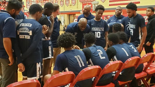 Poughkeepsie head coach Cody Moffett draws up a play during a time out in Saturday's game against Tappan Zee.