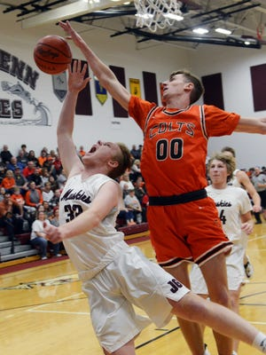 Addy Black, of Meadowbrook, blocks the shot of Braeden Young during the first quarter of John Glenn's 42-32 loss to visiting Meadowbrook on Saturday in New Concord.