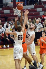 Devan Burris, left, and Ben Judd go up for a block on Johnathan McCall during John Glenn's 42-32 loss to visiting Meadowbrook on Saturday in New Concord.