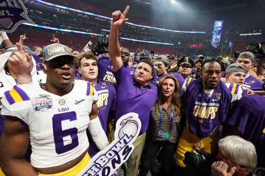 LSU coach Ed Orgeron celebrates with his players and his wife Kelly after defeating Oklahoma in the 2019 Peach Bowl.