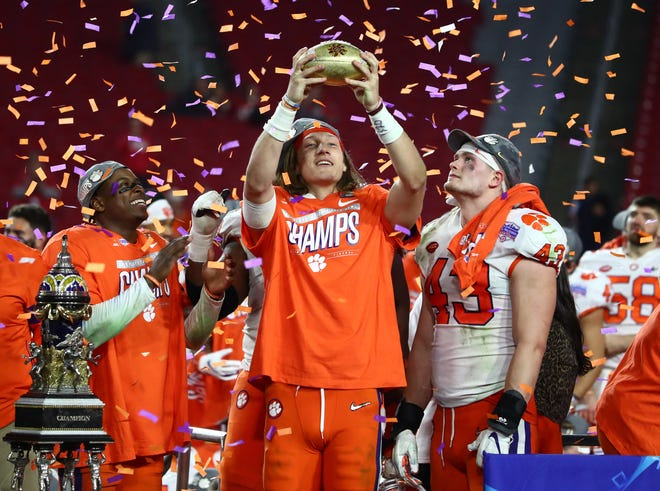 Tigers quarterback Trevor Lawrence (16) celebrates with the trophy after defeating the Buckeyes in the 2019 Fiesta Bowl.
