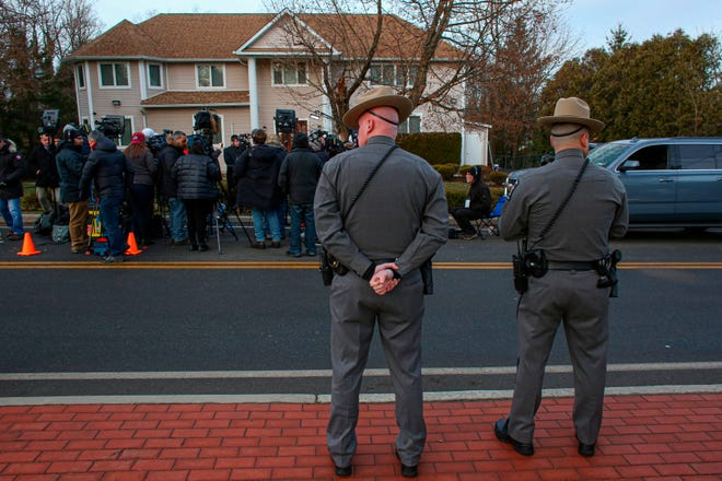 Two police officers stand guard as the press gathers outside a rabbi's home where a machete attack that took place earlier during the Jewish festival of Hanukkah, in Monsey, New York, on Dec. 29, 2019.