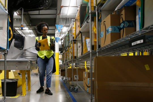 """In this Dec. 17, 2019, photo Tahsha Sydnor stows packages into special containers after Amazon robots deliver separated packages by zip code at an Amazon warehouse facility in Goodyear, Ariz. Amazon and its rivals are increasingly requiring warehouse employees to get used to working with robots. The company now has more than 200,000 robotic vehicles it calls """"drives"""" that are moving goods through its delivery-fulfillment centers around the U.S.  (AP Photo/Ross D. Franklin)"""